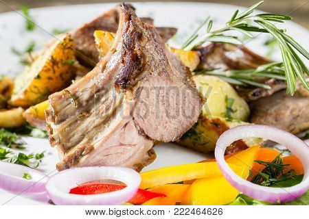 Grilled rack of lamb with fried potatoes and fresh vegetables.