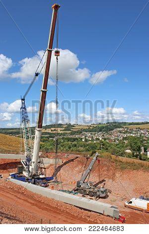 Crane lifting a concrete bridge beam on a construction site