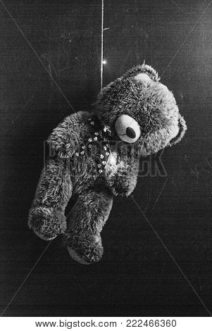 Teddy bear was hung up on a garland, the concept of suicide, a dramatic effect and digital noise, poor holidays