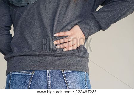 Close-up view of a young woman with pain in kidneys on gray background. Young woman with back ache clasping her hand to her lower back. Woman suffering from ribbing pain, waist pain. Body Concept.
