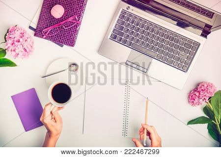 Workspace with laptop, girl's hands writing in notebook, glasses, cup of coffee and wisteria flowers on white background. Top view feminine office table desk. Freelancer working place
