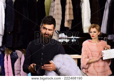 Woman In Pink Fur Coat With Man In Fashion Shop.