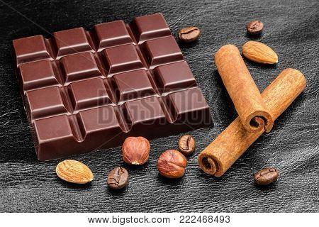 Dark, bitter chocolate bar, almond nuts, hazelnut and two cinnamon sticks on black leather texture background.