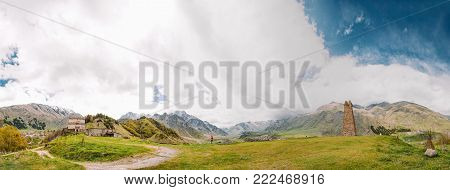 Panorama Of Ancient Church And Old Stone Watchtower On Mountain Background In Sioni Village, Kazbegi District, Mtskheta-Mtianeti Region, Georgia. Spring Or Summer Season. Famous Landmarks And Places In Kazbegi District.