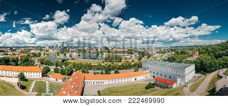 Vilnius, Lithuania. Modern City And Part Of Old Town Under Dramatic Sky In Summer Day. New Arsenal, Foundation Of Church Of St. Ann And St. Barbara, Old Arsenal And Museum of Applied Arts And Design