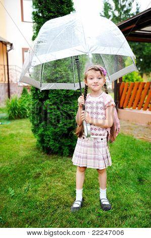 Pequeña colegiala con mochila y paraguas