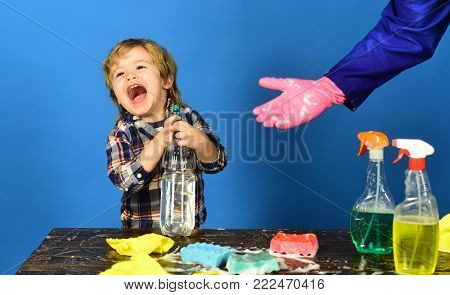 Kid With Laughing Face Holds Spray On Table.