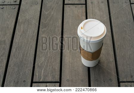 Single hot latte on plank wood floor at relaxing balcony from high angle. Paper coffee cup with plastic sip lid.