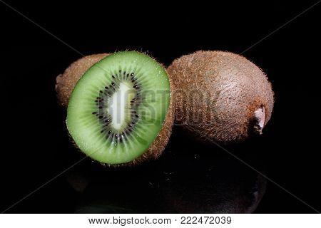 Kiwi kiwis and half kiwi on black background. Studio photo. Green fruit.