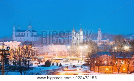 Vitebsk, Belarus. Main Famous Landmarks In Winter Night Cityscape In Evening Illumination Lights. Holy Assumption Cathedral, Holy Resurrection Church And City Hall. Night Panorama With Bright Blue Sky