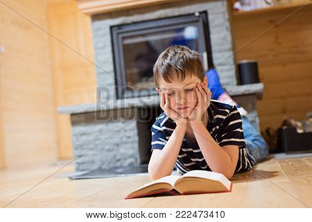 Eight Years Old Boy Reading A Book