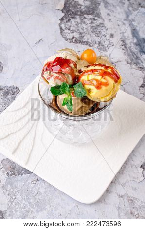 Top view of Dessert - Three balls of multi flavor ice cream with Scoops of Chocolate, Vanilla and Fruit Ice Cream with Fresh Mint in Glass Dish on a white plate on a gray background. Restaurant kitchen, Eating concept
