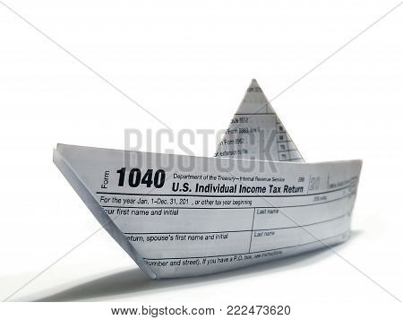 U.S. Individual Income Tax Return form 1040, folded into an origami paper ship facing the viewer to symbolize that tax season is approaching.