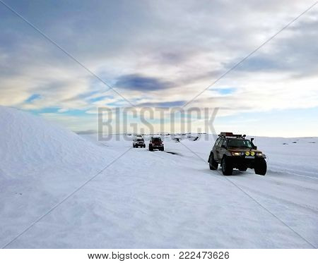 Iceland, February 2017 - A caravan of Icelandic super jeeps off-roads in the snow while taking tourist to the famous ice cave tours, on a cloudy winter day.