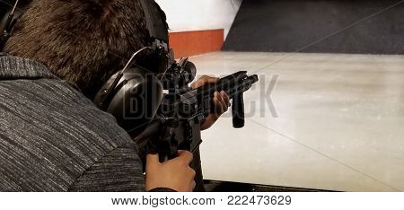 Man at indoor shooting range, with black assault rifle with magnifier scope and black headset.