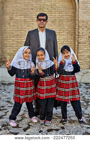 Isfahan, Iran - April 24, 2017: Three unknown smiling Iranian girls of primary school age are photographed with a mature man, father, or teacher.
