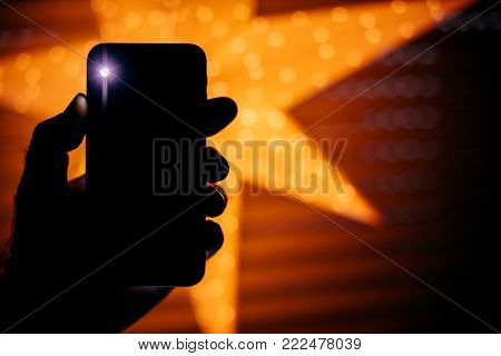 Conceptual shot of man holding the new Phone with yellow star bokeh background featuring a blick light from the rear flash and camera - holiday and technology concept