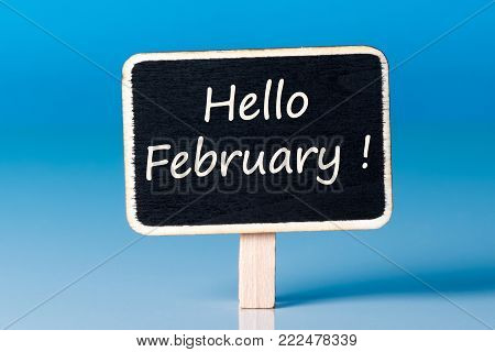 Hello february - message on little wooden tag at blue background. 1st February.