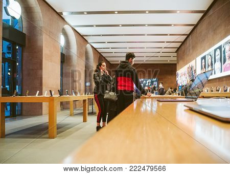 STRASBOURG, FRANCE - JAN 10, 2018: Muslim couple inside Apple Store deciding to buy latest MacBook Pro laptop computer and iPhone X smartphone