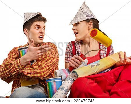 Repair family by happy couple building home. Mad quarrel family of renovation in new apartment by painting tools. Newlyweds in new house. Man in newspaper cap scolds woman for doing stupid things.