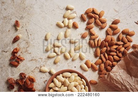 Peeled (blanched) and unblanched whole almonds. Shelled almonds with a small black bowl of blanched almonds.