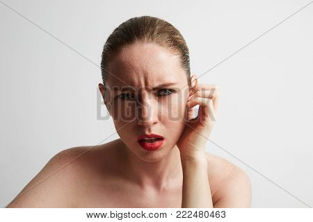 Lovely confused woman against white background. Stressed face.