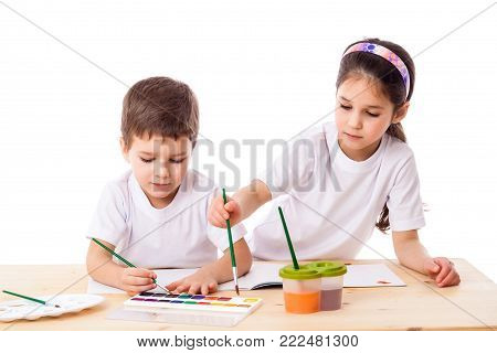 Two kids at the table draws with watercolor together, isolated on white