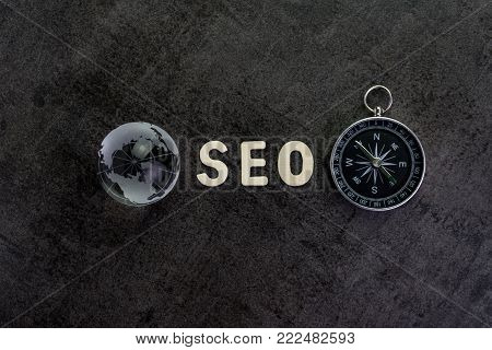 Decoration globe, alphabet SEO and compass on dark cement chalkboard background using as SEO Search engine optimization concept.