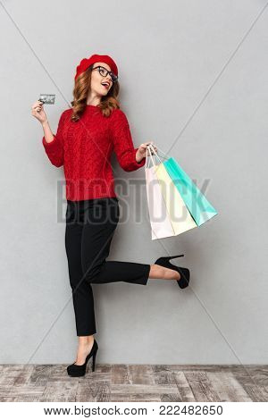 Full length portrait of a smiling woman dressed in red sweater and eyeglasses showing credit card while walking with shopping bags isolated over gray wall background