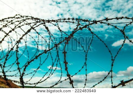 Barbed wire. Barbed wire on blue sky background with white clouds. Wire boom. Military conflict . Syria.