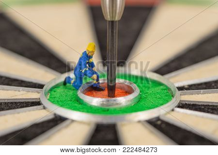 Miniature People With Dart In Bull's Eye, Close Up