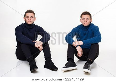 Casual twin brothers. Two brothers are sitting on the floor. Studio shot on a white background