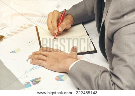 business man sitting writing text note black cover on graph diagram paper, he wear gray suit and use red pen on work table at office