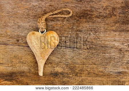 Hand crafted wooden heart with rope to hang on rough weathered wood background with copyspace