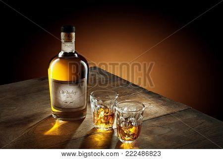 SELF MADE LABLE.  view of glass of  whiskey and a bottle aside on color background.