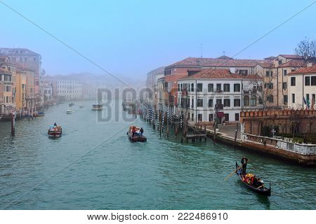 VENICE, ITALY - FEBRUARY 17, 2017: Boats and gondola on misty morning on Grand Canal in Venice - famous tourist destination and place of traditional annual Carnival.