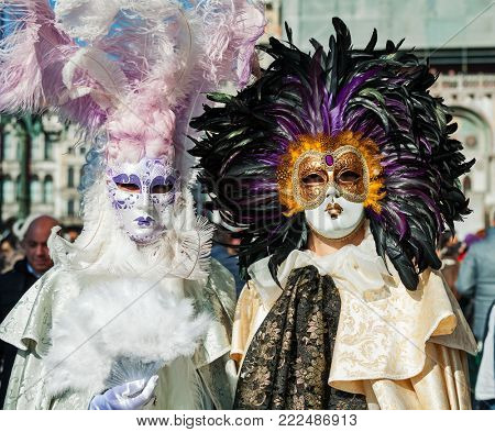VENICE, ITALY - FEBRUARY 18, 2017: Two unidentified participants wear traditional vintage costumes and masks with feathers during famous Carnival taking place each year on february in Venice, Italy.