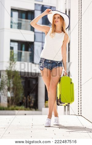 Travel, adventure, teenage journey concept. Walking woman wearing denim shorts, white top and sun hat suitcase holding suitcase on wheels