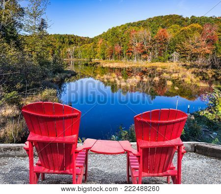 Magnificent resort in French Canada. Red plastic loungers on the shore of the pond. Foliage of forests is reflected in the pond. Concept of ecological tourism