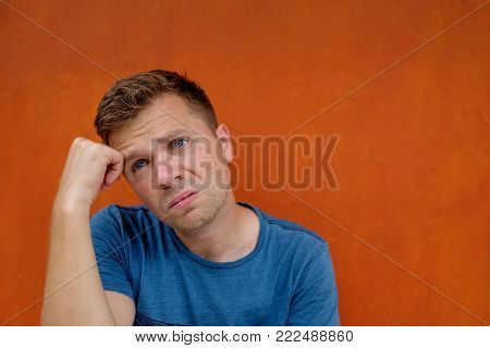 Close up portrait of caucasian disappointed stressed young man on red background. He is about to cry. Negative human emotions