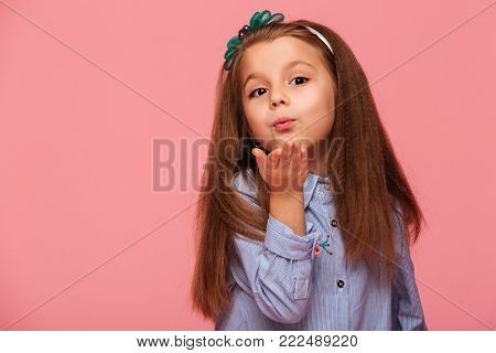 Portrait of adorable little girl 5-6 years with beautiful long auburn hair, blowing air kiss on camera over pink background