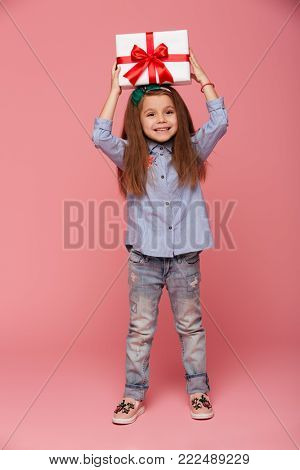 Full-length portrait of joyous female kid holding gift box with red ribbon bow on her head, feeling pleasure over pink background