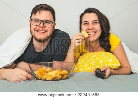 man with woman watchin TV in bed while eating snacks