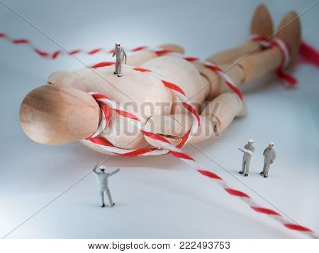 Miniature people: Miniature workers helped move the giant wooden doll. Concept image. Selective focus
