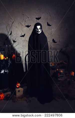 Mystic creature in black cloak in darkness