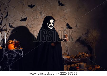 Mystic creature in black cloak holding candle in darkness