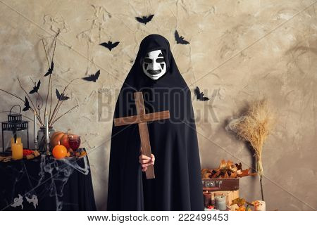 Mystic creature in black cloak holding cross indoors