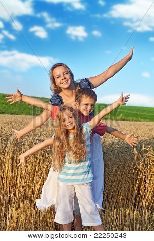 Woman and kids having fun in the wheat field in summer time