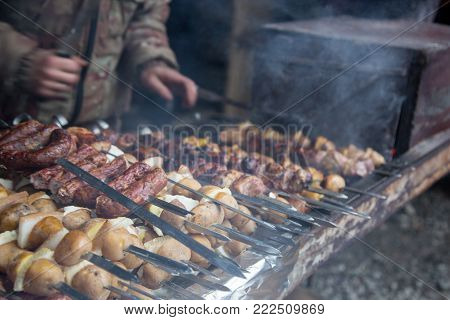 The cook prepares meat on the skewer and tests the readiness of the meat with a large knife.