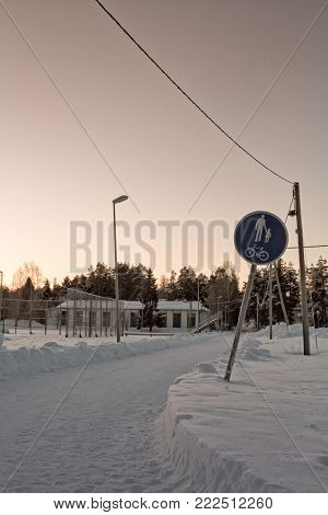 The walkway to the town has been covered with heavy snowfall in the Northern Finland. The traffic signs are frozen completely.